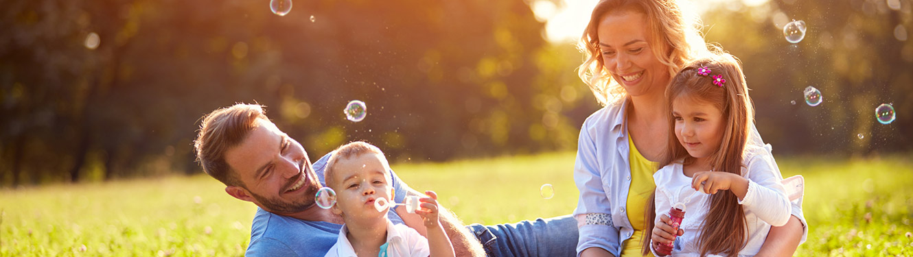 Family blowing bubbles in a field