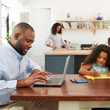 Family in kitchen, husband using laptop computer